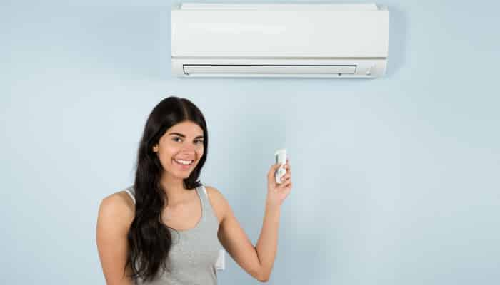 Woman Holding Remote Control In Front Of Air Conditioner